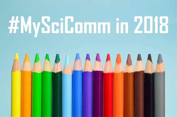 "A line of colored pencils, one in each of the common colors on the rainbow spectrum. Text on the image reads ""#MySciComm in 2018."""
